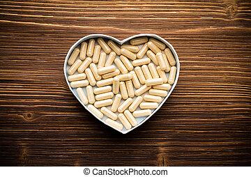 Pill. - Pill, heart-shaped box. Wooden surface.
