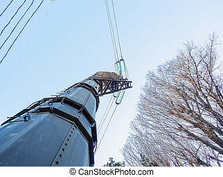 Pillar with electric wires and trees against the blue sky. Photo below