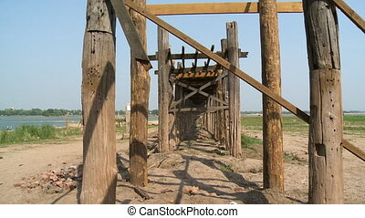 Pillars of a wooden bridge overlooking a field - A close up...