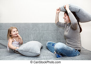 Pillow fighting on the sofa.