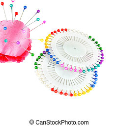 Pillow for needles and bright colored pins isolated on white background.