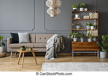 Pillows and blanket on beige couch in grey living room interior with wooden table and plants. Real photo