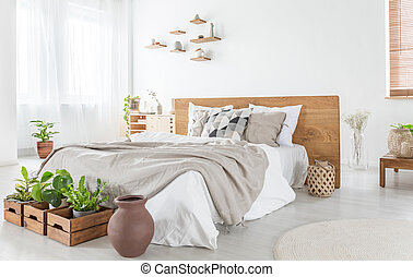 Pillows and sheets on wooden bed in bright bedroom interior with plants and windows. Real photo
