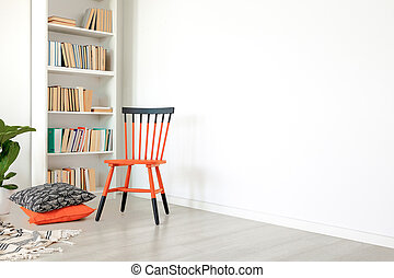 Pillows next to orange and black chair in white room interior with copy space on empty wall. Real photo