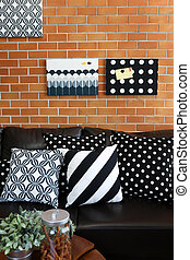 Pillows on a sofa with brick wall in background