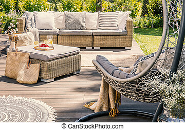 Pillows on rattan couch and table on patio with hanging chair during summer. Real photo