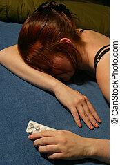 """A """"junkie"""" girl asleep with an empty packet of pills / tablets in her hand."""