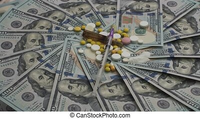 Pills, ampoules, narcotics and syringes rotating on money -...