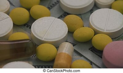 Pills and ampoules rotating on money - healthcare cost...