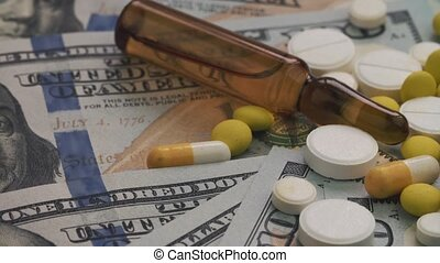 Pills and ampoules rotating on money - healthcare cost concept. Close-up