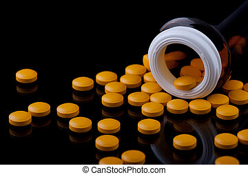 Pills and bottle - Yellow pills and a bottle on a black ...