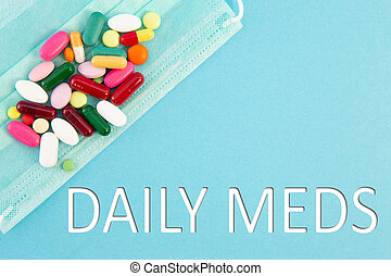 Pills and surgical mask with daily meds text