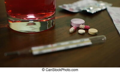 pills and thermometer on the table