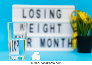 Pills for weight loss on a blue background