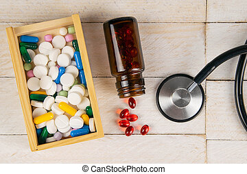 Pills in botle and wooden box with stethoscope and heart on white wooden table. Medical concept. Top views with clear space