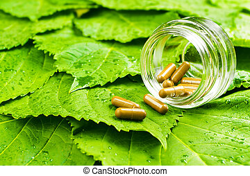 Pills in jar over green leaves. Healthy vitamin concept