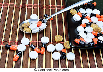 pills in spoon on table