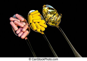 Pills in three spoons on black background - pharmaceutical concept. Selective focus
