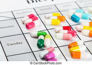 pills of different colors on a calendar
