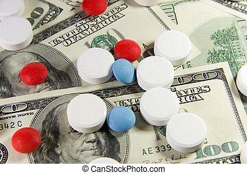 Pills on a bunch of US dollars - Closeup of white, red and...