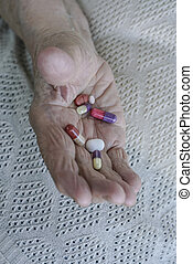 pills on palm of a senior woman