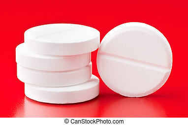 Pills on red background