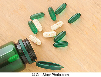 Pills spilling out of a bottle on wooden