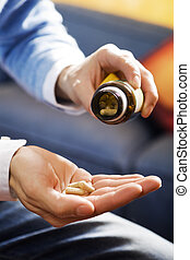 pills - healthcare and medicine: man taking a painkiller
