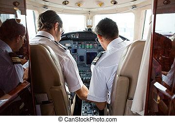 Pilot And Copilot In Cockpit Of Corporate Jet