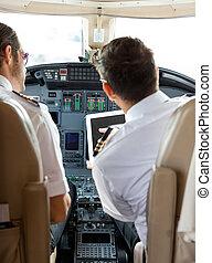 Pilot And Copilot Using Digital Tablet In Cockpit - Rear...