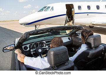 Pilot And Stewardess In Convertible Parked Against Private Jet