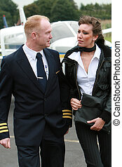 Pilot and young woman in front of a private airplane