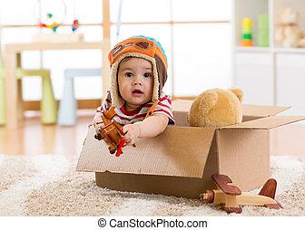 Pilot aviator baby boy with teddy bear toy plays in cardboard box