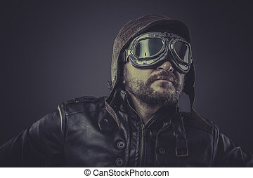 pilot dressed in vintage style leather cap and goggles