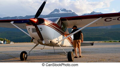 Rear view of pilot examining aircraft near hangar 4k