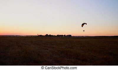 Pilot flying a paraglider with a motor at sunset, the camera...