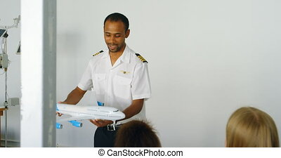 Pilot giving training about model aeroplane to kids 4k -...