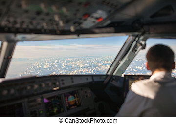Pilot in a commercial airliner airplane flight cockpit during flight