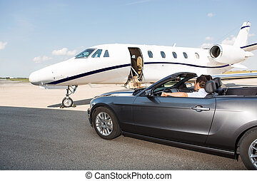 Pilot In Convertible Parked Against Private Jet - Pilot in...