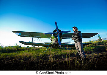 Pilot in front of vintage plane