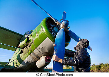 Pilot is repairing engine of vintage plane with the wrench.