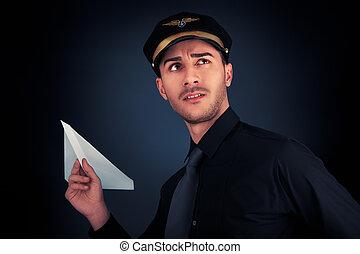 Pilot Launching Paper Airplane - Young pilot wearing black...