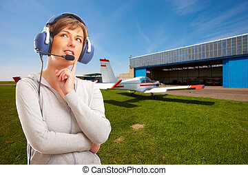 Pilot with headset outside - Cheerful woman pilot with...