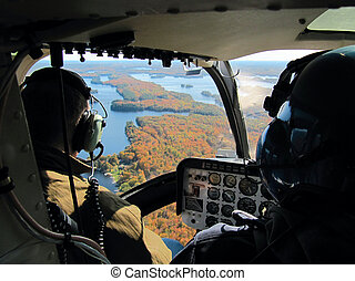 Pilots in the cockpit of the helicopter flying over the Great Lakes