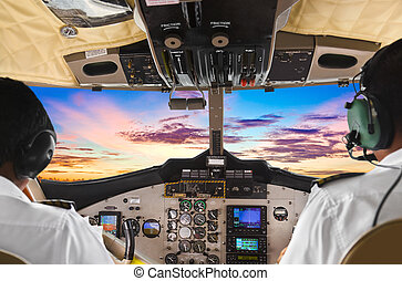 Pilots in the plane cockpit and sunset - Two pilots in the ...