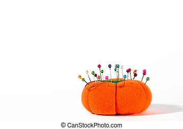 Colorful pins on pin cushion against white background. Plenty of copyspace.