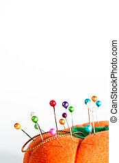 Colorful pins on pin cushion against white background. Plenty of copy space. Portrait orientation.
