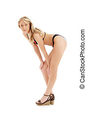 pin-up blond in platform shoes and black bikini over white