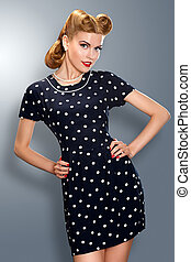 Pin-up girl in retro vintage old-fashioned dress posing -...