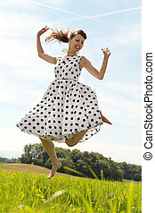 Pin up Girl jumping in the meadow